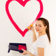 The young woman draws red paint heart — Stock Photo
