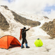The climber costs on glacier near tent — Stock Photo #32449957