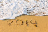 New Year 2014 is coming concept. Inscription 2014 on beach sand. — Stock Photo