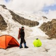 The climber costs on glacier near tent — ストック写真