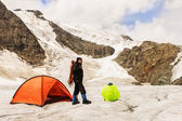 The climber costs on glacier near tent — Stock Photo