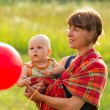 Mother on walk with the small child in ringsling — Stock Photo
