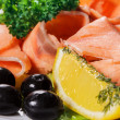 Slices of red fish with lemon and olives on plate — Stock Photo