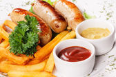 Sausages a grill with French fries and fennel — Zdjęcie stockowe
