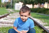 Lonely little boy sitting on a rails — Стоковое фото