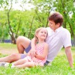Foto Stock: Father and daughter sitting together on grass