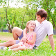 图库照片: Father and daughter sitting together on grass