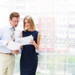Постер, плакат: Business man and business woman in the office to discuss reports