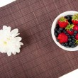 Stock Photo: Strawberries, bilberry and flower on bamboo tablecloth