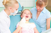 Female dentists examines a child — Stock Photo