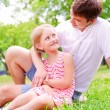 Father and daughter sitting together on the grass — Stock Photo #13655201