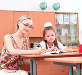 Teacher sitting near pupil — Stock Photo