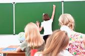 School girl writes on the blackboard — Stock Photo