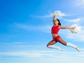 Young cheerleader in red costume jumping — Stock Photo