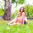 Stock Photo: Mother and daughter sitting together on grass