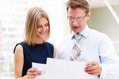 Business man and business woman in the office to discuss reports — Stock Photo