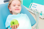 Girl in the dentist's chair shows a green apple — Zdjęcie stockowe