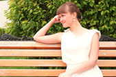 A beautiful woman is sitting on a park bench — Stock Photo