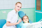 Young doctor woman and girl in dentist office — Stock Photo