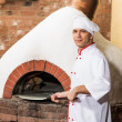 Chef puts dough in the oven for pizzas, — Stock Photo #15631645
