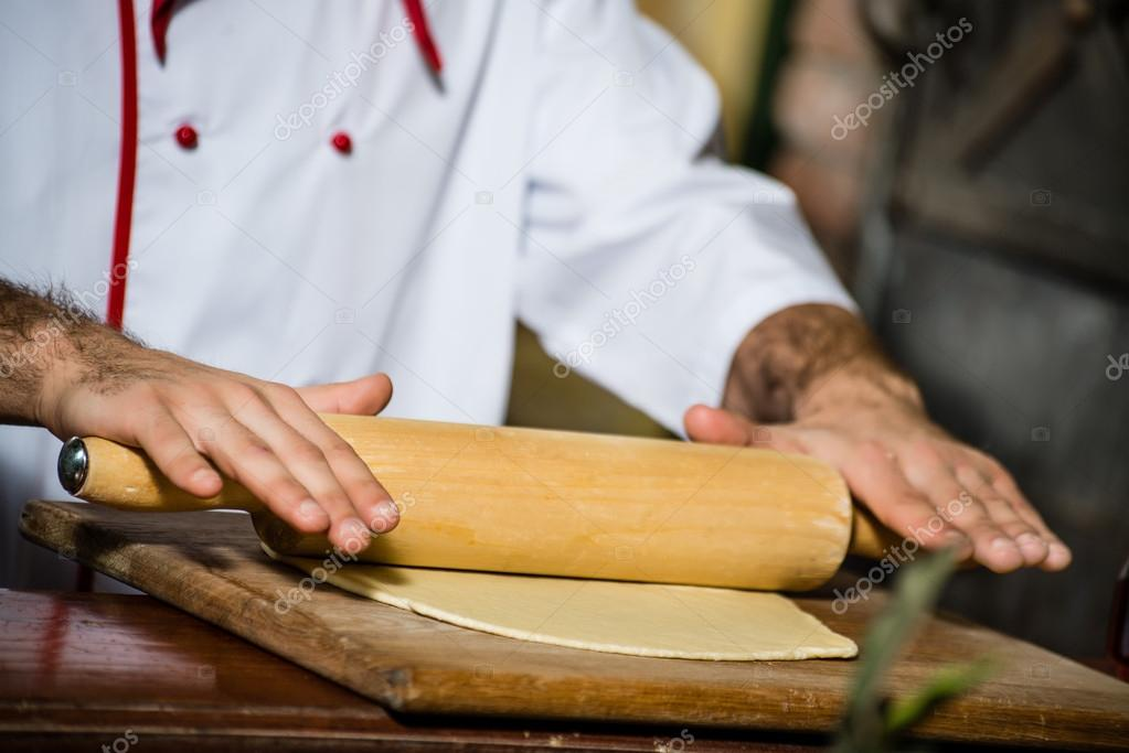 Cook man rolls the dough with a rolling pin, for pizzas — Stock Photo #15630847