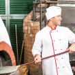 Chef puts dough in the oven for pizzas, — Stock Photo