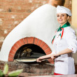Royalty-Free Stock Photo: Chef puts dough in the oven for pizzas,