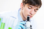 Milled scientist looking into a microscope — Stock Photo