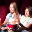 Two young girls watching in cinema — Stock Photo #16259165
