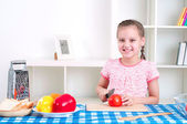 Girl working in the kitchen cutting vegetables — Stock Photo