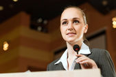 Business woman speaks into a microphone — Stock Photo