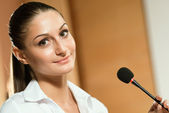 Portrait of a business woman with microphone — Stock Photo