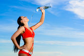 Sport girl in red uniform with a bottle of water — Stockfoto