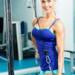 Young womdoing body-building in Gym — Stock Photo #17656597