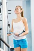 Young woman doing body-building in the Gym — Stockfoto