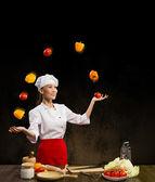 Woman-cook juggleing vegetables. — Stock Photo