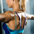 Female athlete straining back muscles and arms — Stock Photo #18003899
