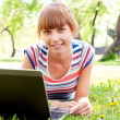 Girl in park with laptop — Stock Photo
