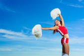 Young cheerleader in red costume with pampon — Stock Photo