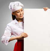 Female chef holding a poster for text — Stock Photo
