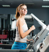 Attractive young woman runs on a treadmill — Stock fotografie