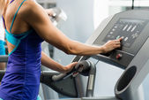 Woman adjusts the treadmill — Stock Photo