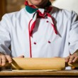 Royalty-Free Stock Photo: Cook rolls out the dough on a board