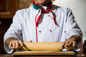Cook rolls out the dough on a board — Stock Photo