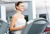 Attractive young woman runs on a treadmill — 图库照片