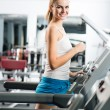 Stock Photo: Attractive young womruns on treadmill