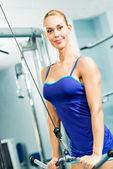 Jonge vrouw doen lichaam-gebouw in de sportschool — Stockfoto