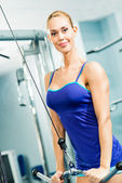 Jovem mulher fazendo musculação na academia — Foto Stock