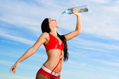 Sport girl in red uniform with a bottle of water — Stock Photo