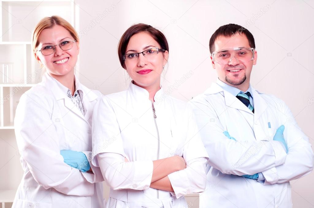 Three doctors are smiling at the camera in a doctors' office. Horizontally framed shot.  Stock Photo #18875631